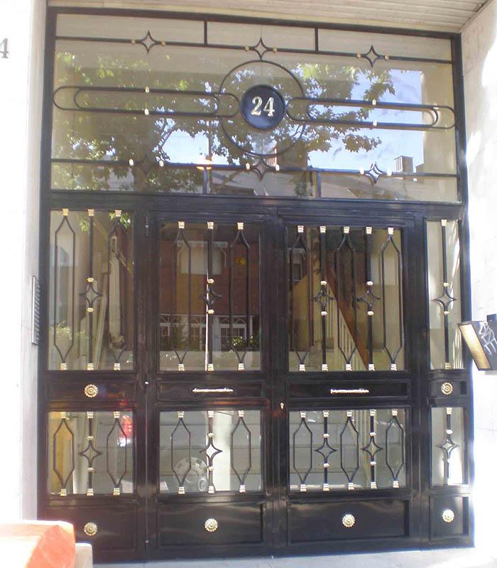 Puerta de comunidad de propietarios acristalada con elementos decorativos por Cerrajería Keymar